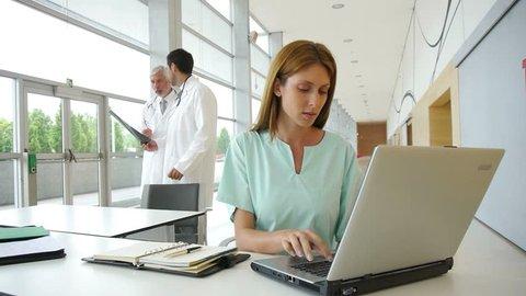Nurse working on laptop computer in hospital