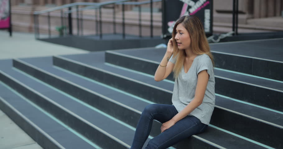 Young Asian woman in city talking on cell phone | Shutterstock HD Video #11595704