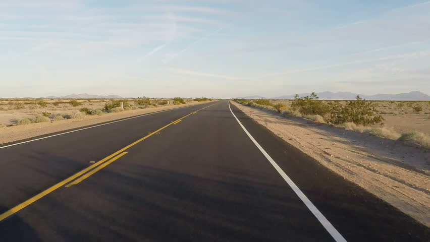 Point of view vehicle driving shot of California Highway 62 through the Mojave desert. Viewpoint of driver over smooth blacktop asphalt on a stretch of desert highway.