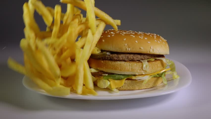 Fried potato chips falling down on hamburger, slow motion, fast food, junk food concept.