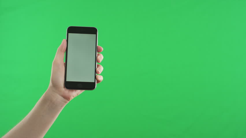 Female hand holding the newest smartphone on original green screen background. The last phone model. You can track it easily putting the trackers on the screen corners. Cinema frame rate 23.97fps. | Shutterstock HD Video #11612684