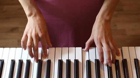 Woman hands playing on synthesizer, top view close up