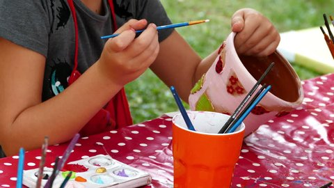 TIMISOARA, ROMANIA - SEPTEMBER 5, 2015: Girl who paints a ceramic bowl. Workshop organized by the City Hall with the occasion of the City Day.