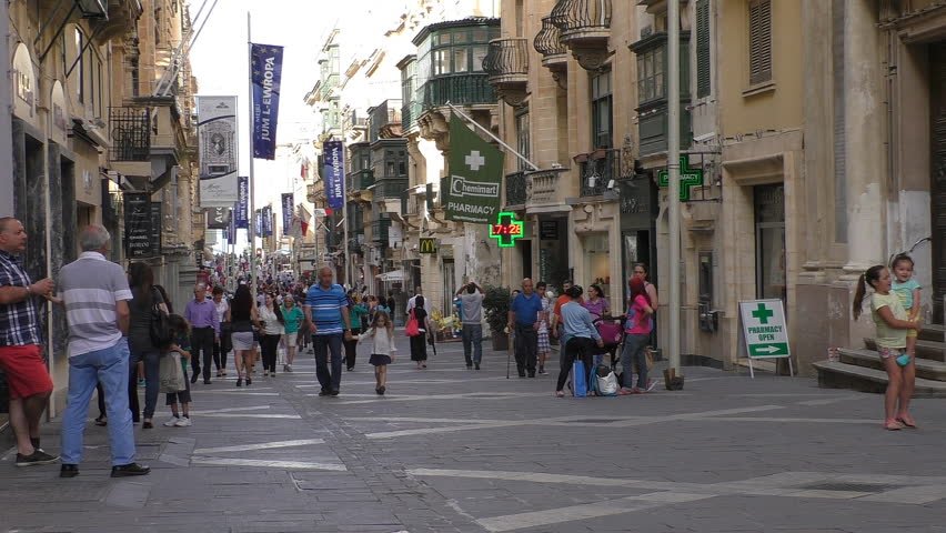 MALTA CAPITAL VALLETTA CITY CENTRE CENTER, PEDESTRIAN STREET - MAY 2015: Many tourist and local people shopping in the old downtown full of shops, cafe, pharmacy; kids playing, friends chatting