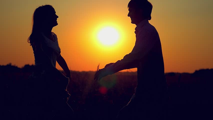 slowmotion of silhouette of couple hugging whirl in happiness on the field at sunset 1920x1080