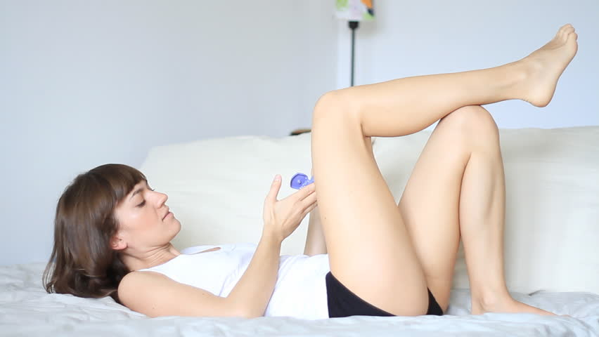 Woman applying moisturizer cream on her legs