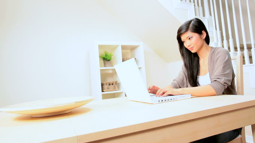 Young asian girl using a laptop in her home setting