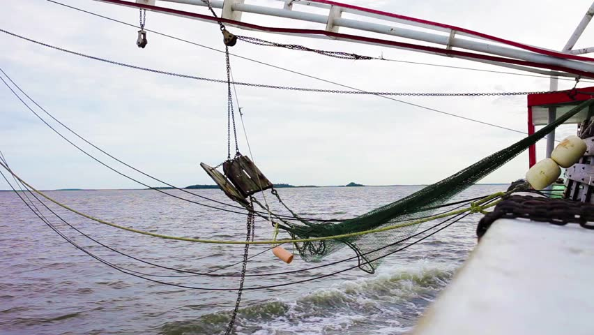 View of the side of a commercial fishing vessel with nets over water