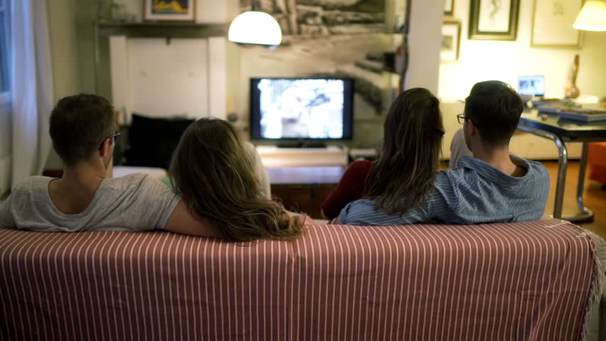 Two couple watching tv and chatting at home