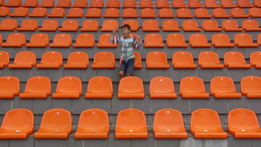 Boy sitting at the stadium and glad his team scored a goal. happy boy watching match at stadium, boy shows emotion, the boy sits alone in the stadium hockey, ice hockey, soccer, basketball, volleyball | Shutterstock HD Video #11787284