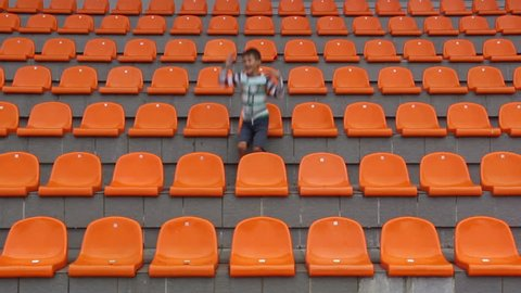 boy sitting at the stadium and glad his team scored a goal. happy boy watching match at stadium, boy shows emotion, the boy sits alone in the stadium hockey, ice hockey, soccer, basketball, volleyball