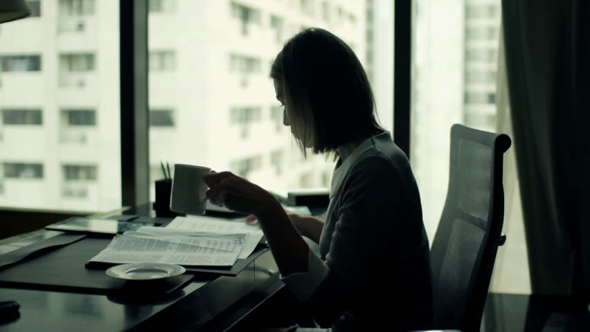 Young businesswoman reading documents and drinking coffee while sitting by desk in office