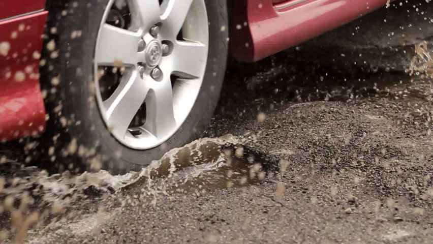 Car Hits Two Pot Holes. slow motion of a car driving through two potholes filled with water. splashing everywhere.
