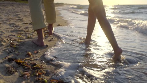 Couple Walk Along Beach, Closeup Of Legs/Bare Feet, Waves Crash At Their Feet