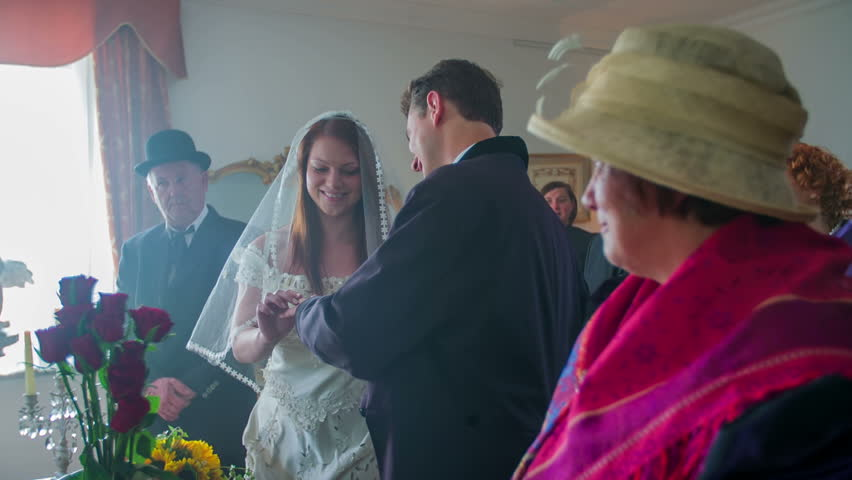 The groom puts a ring on his fiance's finger, the same does the bride. They both kiss each other as the have just gotten married. The guests at the wedding ceremony as clapping.  | Shutterstock HD Video #11847434