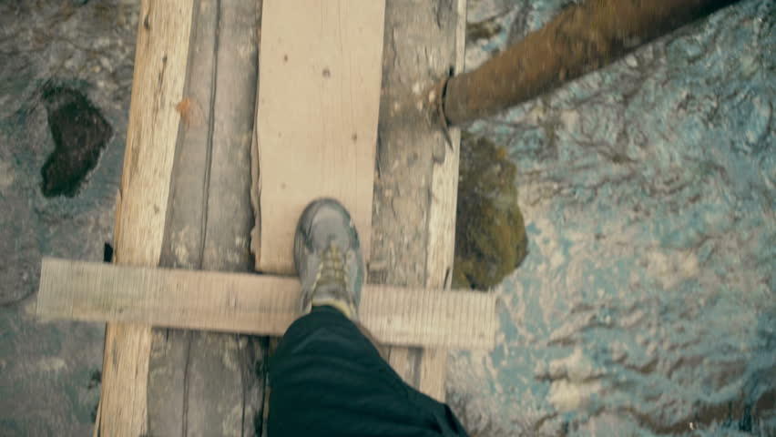 A man walking on small bridge over river in forest, point of view perspective