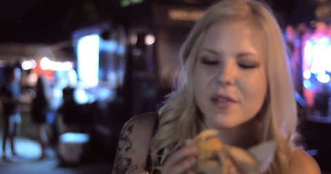 4K -A Close up shot of pretty girl eating a burger from a popular food truck in a fun urban street festival setting at night.