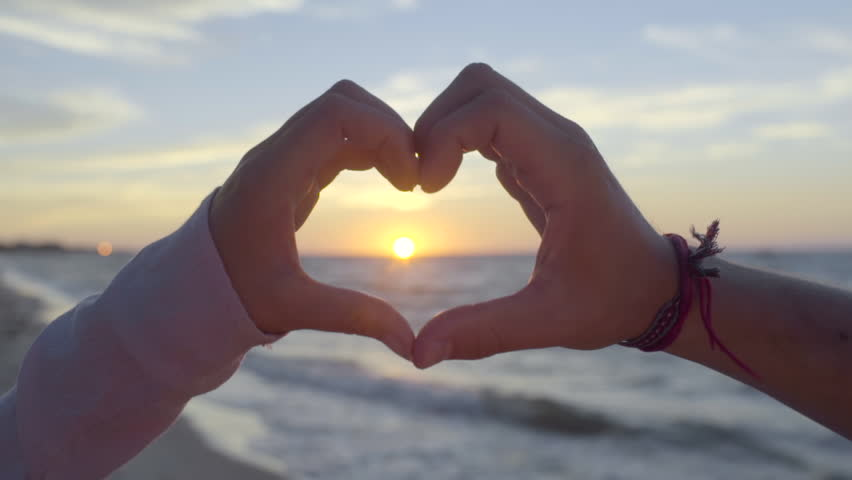 Young Couple Make The Shape Of A Heart Around Sun At Sunset On Beach Stock Footage Video 11859764