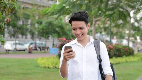 Happy Asian young student using mobile phone to online, texting, sms, outdoor green park.