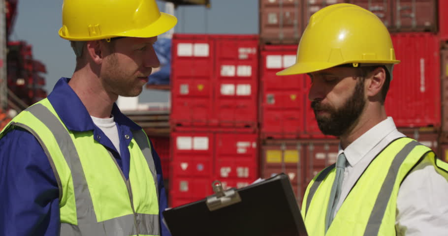 Businessman and dock worker shake hands at a busy shipyard. Shot on RED Epic.