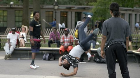 NEW YORK - SEPT 25, 2015: b-boy doing breakdancing moves, spinning on elbows and hands in Washington Square Park in 4K NY. Washington Square Park is a famous public park in Manhattan NYC.
