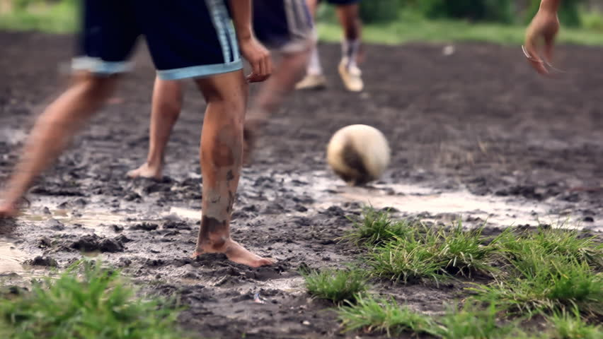 A gang of bar feet kids playing soccer on a muddy field. Serial of slow motion shots with depth of field effects. Action loaded details of running legs and goal shots. [b]HD1080 | 30fps[/b] | Shutterstock HD Video #1191613