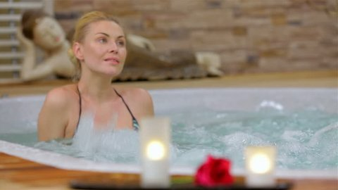 Spa resort jacuzzi hot tub woman. Happy woman relaxing in jacuzzi. Woman in spa salon.