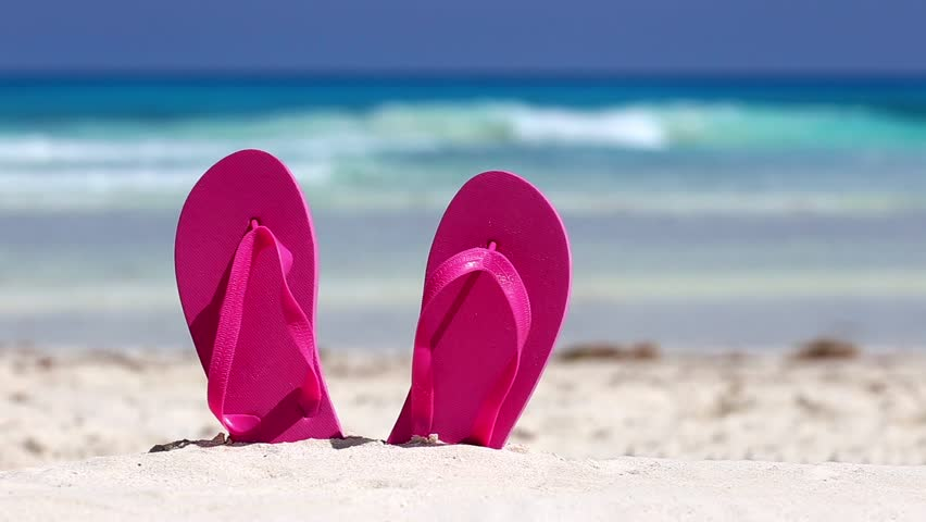 Pink flip flops on white sandy beach near sea waves, nobody. Summer vacation concept