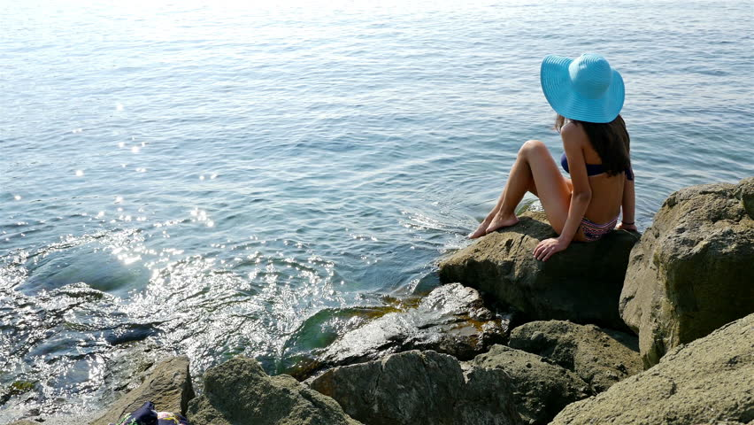 Young woman in swimming suit and blue hat sitting on rocks on the sea shore | Shutterstock HD Video #11951021