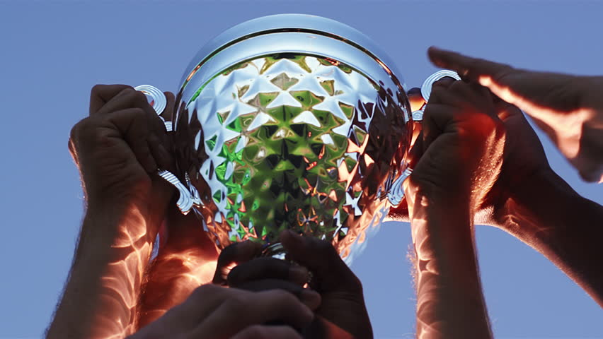 Close up of a trophy being held in the air by a sports team