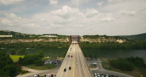 Aerial camera moves toward the 360 penny backer bridge. Traffic is normal on the road, while boats cross the water. The camera moves above the bridge and the camera eventually points down.