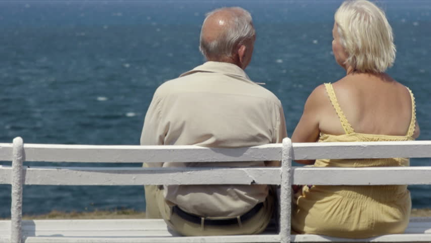 senior caucasian couple sitting on bench near the sea and hugging