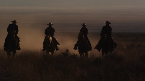 Slow motion panning shot of four cowboys riding horses, leaving a trail of dust. This was shot in slow motion at sunset using a high speed camera.