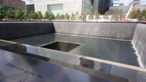 NYC - SEP 8, 2014: Square waterfall memorial of people killed in terrorist attacks on September 11, 2001 and skyscrapers
