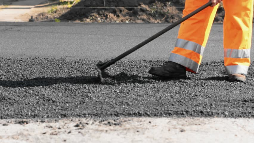 Road construction worker leveling asphalt using rake while in the back road roller passing by
