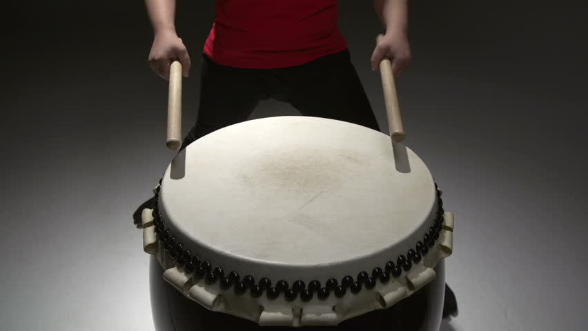 anonymous girl playing Taiko performs at the drum, increasing the rhythm, sound, abstract background in the Studio