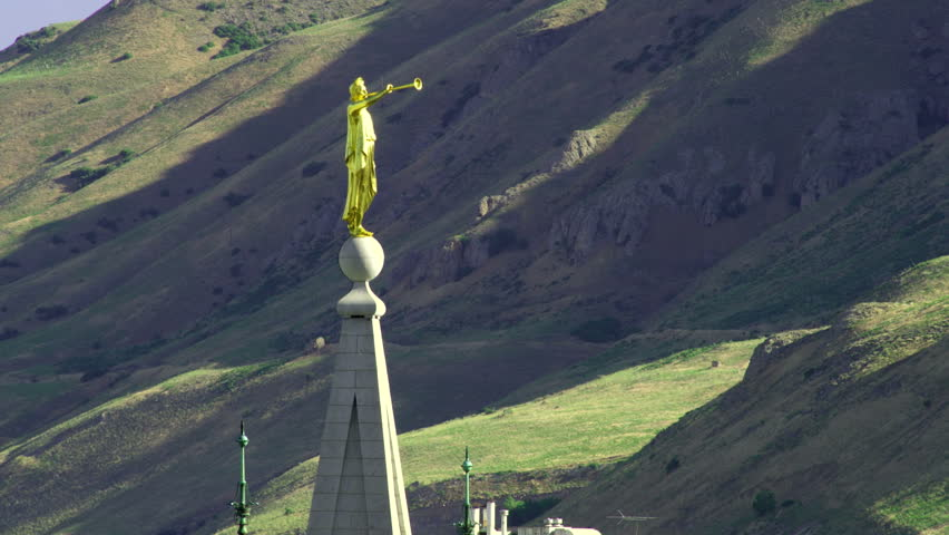 The golden-colored statue of Angel Moroni points eastward on top of the LDS Salt Lake Temple. The green and brown mountains can be seen in the background.