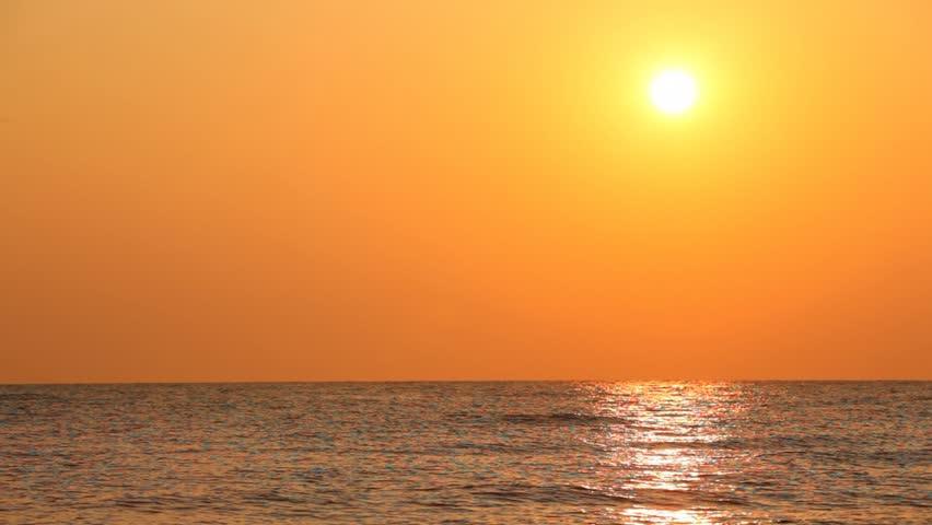 beautiful sunset against orange sky over quiet sea waves