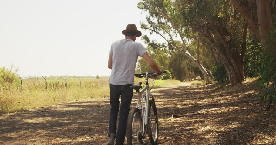 Hispanic Man Walking Down Trail With Bike Stock Footage Video