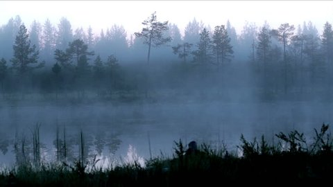 Early morning fog and mist above a quiet lake in Finland timelapse