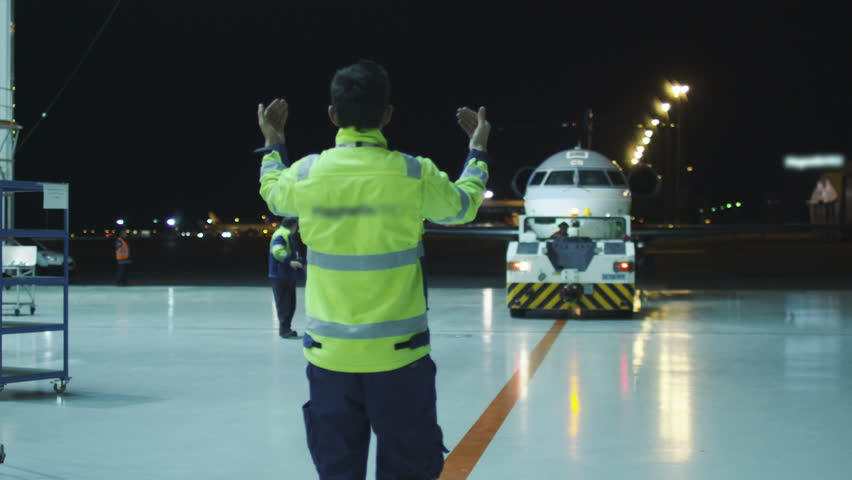 Aircraft marshal directs an airplane in the night to move towards hangar. Shot on RED Cinema Camera in 4K (UHD).