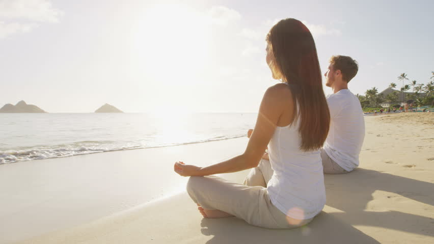Meditation. Yoga people by the sea relaxing in serene zen lotus yoga pose on a beach at sunrise. Woman and man meditating together.
