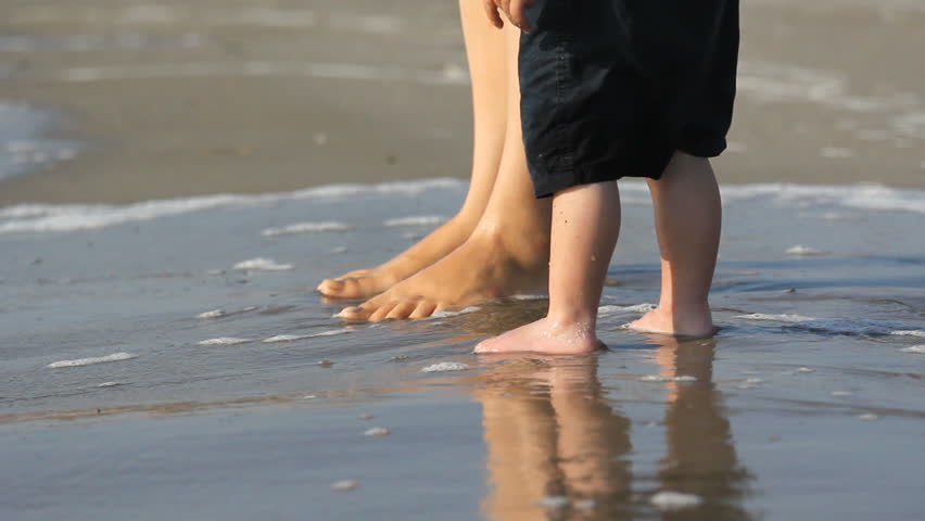 Mother and baby child feet on seashore, sea waving coming back and fort to shore | Shutterstock HD Video #12208064