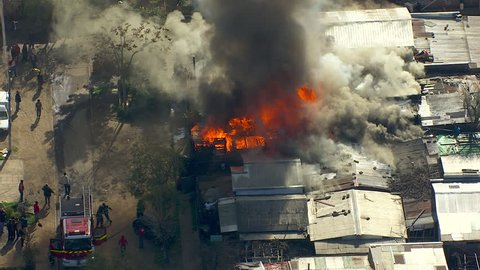 MS AERIAL Shots of house burning in shanty town / Santiago, Central Valley, Chile