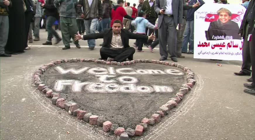 "CAIRO - CIRCA FEB 2011: Man with ""Welcome to Freedom"" sign at Tahrir Square, circa February 2011, Cairo, Egypt. Tahrir Square was the focal point of the 2011 Egyptian Revolution where demonstrations grew to 250,000 plus people by day 6, January 31, 2011."