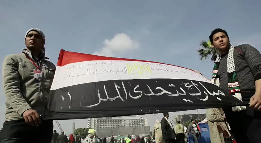CAIRO - CIRCA JAN 2011: Two men carrying Egyptian flag, Tahrir Square, circa January 2011, Cairo, Egypt. Tahrir Square was the focal point of the 2011 Egyptian Revolution where demonstrations grew to 250,000 plus people by day 6, January 31, 2011.