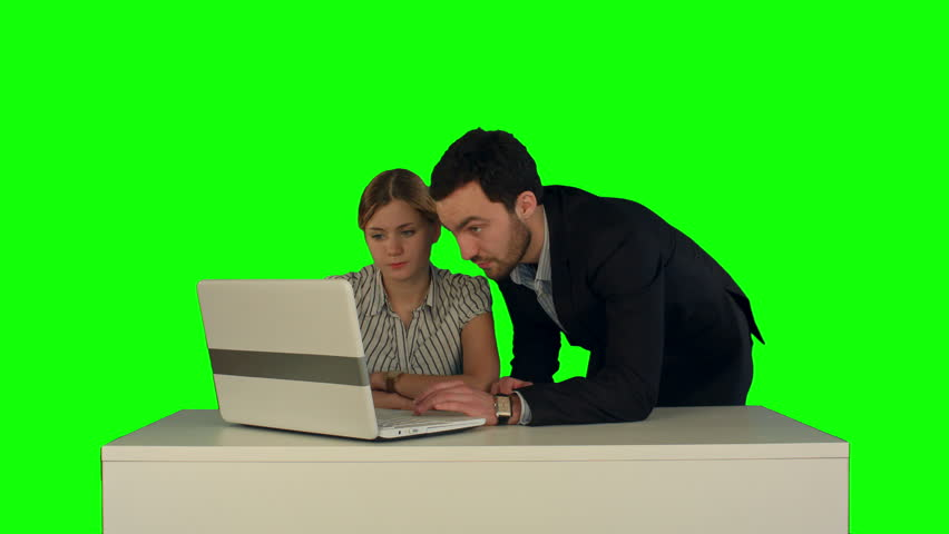 Couple discussing new project on the laptop. Teamwork concepts. on a Green Screen, Chroma Key. Professional shot on BMCC RAW with high dynamic range. You can use it e.g in your commercial video