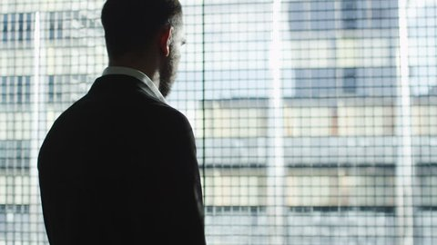 Businessman in a suit stands next to a big window and uses smartwatch on a sunny day. Shot on RED Cinema Camera in 4K (UHD).