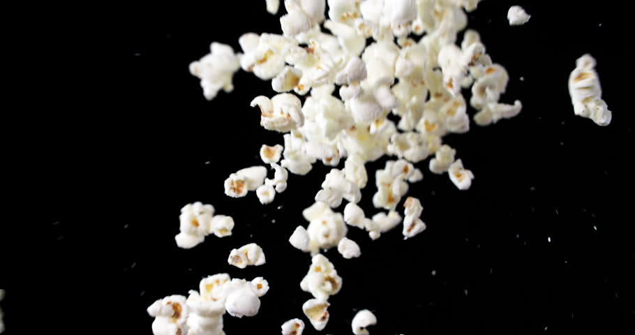 Healthy Popcorn snack tossed up and falling down in slow motion against black background, 240fps movie watching snack