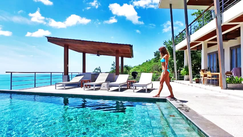 Beautiful woman walking around pool. Nice sea view from luxury villa. Legs.